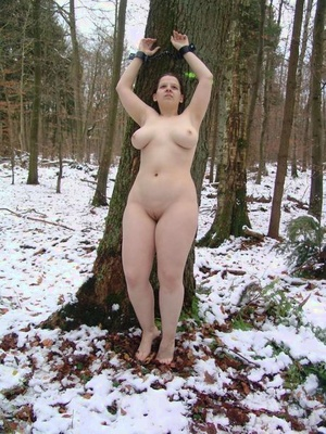 Busty woman slave is affixed nude to tree in winter and pallet indoors