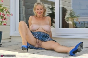 Older blonde exposes her huge boobs as she undresses to masturbate on patio