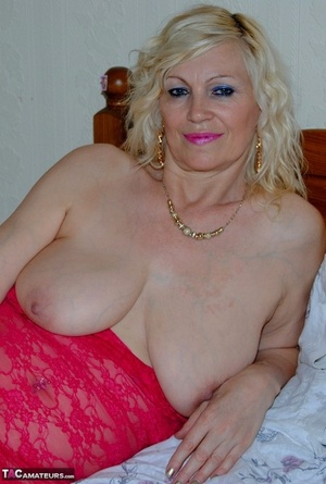 Mature sexy Platinum Blonde pulls down red lace dress to expose huge saggy knockers