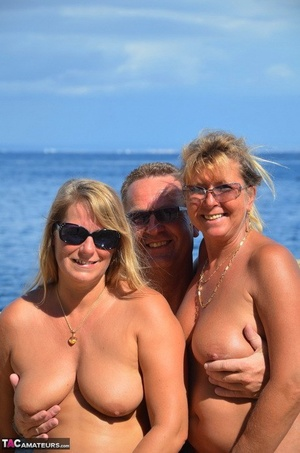 Two blonde women with saggy tits enjoy steamy suck and fuck in beach threesome