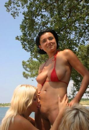 Big titted women partake in a lesbian threesome on a sandy beach