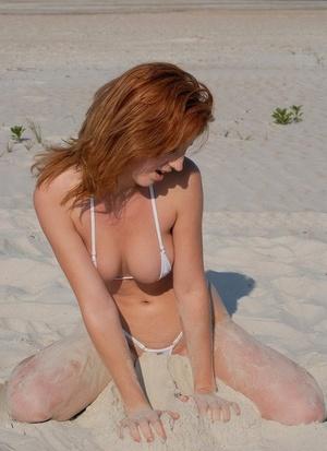Sexy redhead Stephanie in skimpy bikini flaunting her hot wares on the beach