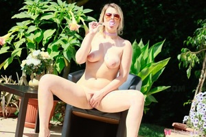 Blonde amateur Nikky Dream blows a kiss while posing naked in sunglasses