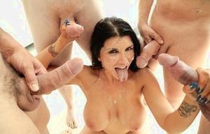 Dark haired chick Romi Rain gargles off a group on men on her knees