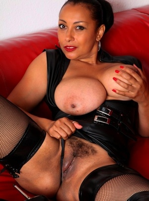 Busty mature woman Danica Collins fingers her pussy in OTK boots