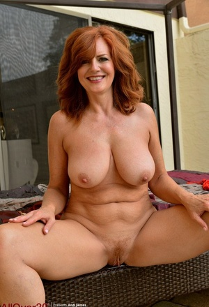 Mature redhead Andi James cups her innate tits while posing nude in heels