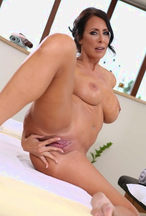 Middle-aged black-haired woman Reagan Foxx exposes her large boobs as she strips