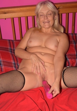 Hot mature lady with blonde hair toys her bald pussy in mesh stockings