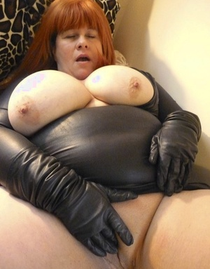 Fat older redhead Mrs Leather feels her huge tits and twat with leather gloves