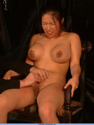 Naked Asian girl with big boobs has clothespins attached to twat before needle play