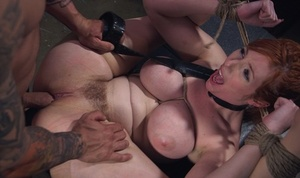 Huge-boobed redhead Lauren Phillips is gagged and tied up with rope for a hard fuck