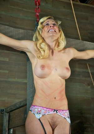 Busty slave hung on cross and tortured with tongue clip & other harsh implements