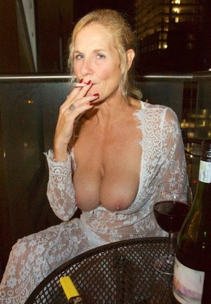 Mature woman Molly MILF works free of lace dress while smoking and drinking