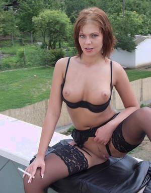 Smoking hot redhead in stockings licks her firm hard nipples on the rooftop