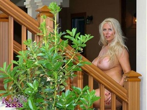 Large blonde Karen Fisher stands naked in parking lot while modeling naked