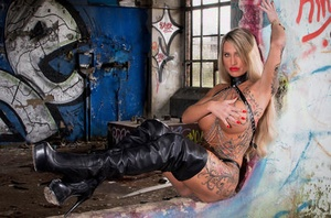 Tattooed blonde with yam-sized boobs models solo amid graffiti packed walls