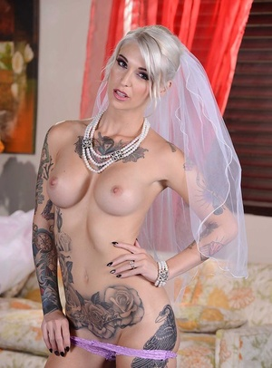 Stunning blonde bride in glamorous dress uncovering her tattooed curves