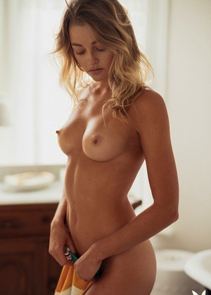 Blonde girl Megan Samperi uncovers her firm boobs as she disrobes for Playboy