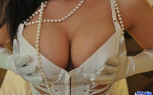 Sweet Krissy in white leather & lace lingerie disrobes to pose naked in gloves