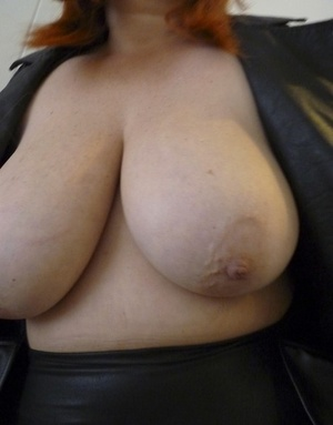 Fat redhead Mrs Leather bares hefty titties before a cumshot on leather trousers