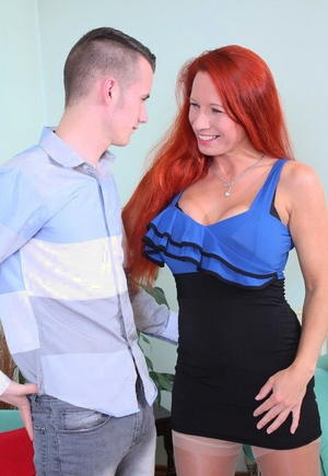 British cougar with red hair kisses her toy boy before undressing him