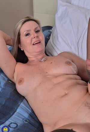 Middle aged woman shows her neighbor's guy the ways of sex in her bedroom