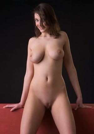 Buxomy grinning Ashley lets her large big tits hang while posing stark naked