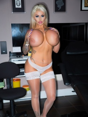 Bombshell Candy Charms flaunts her large silicone jugs and hot shaved pussy
