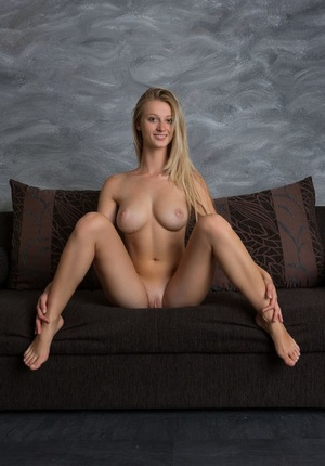 Busty stunner Carisha chilling nude on the sofa showing her molten assets