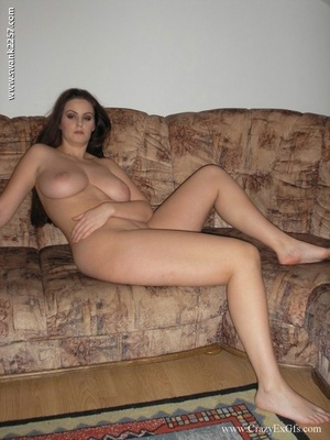 Brunette amateur uncups her big natural tits as she undresses on couch
