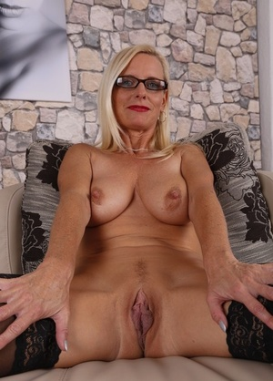 German housewife Tina in black stockings masturbating her pussy on the sofa