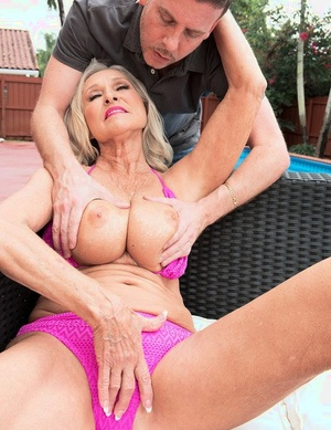 Sexy granny with big boobs catches the attention of the swimming pool cleaner