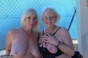 Mature ladies go topless while while humping each other on bar stools