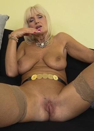 Older blonde woman Roxanna C strips to stockings prior to masturbating
