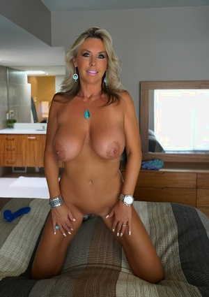 Big-boobed blonde housewife draped naked across the bed toying her horny pussy