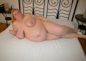 Obese light-haired woman washes cum after breasts in the bathtub after fucking