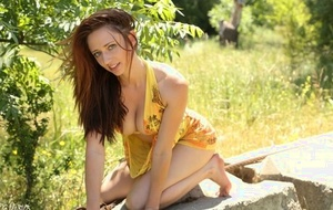 Pallid redhead Lily Xo models bottomless outdoors in bare feet on concrete bench