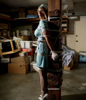 Blonde nurse Carissa Montgomery has her great tits exposed while bound to post
