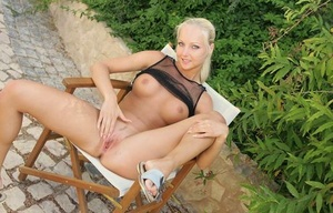 Platinum blonde damsel with firm knockers strokes her pussy on patio chair