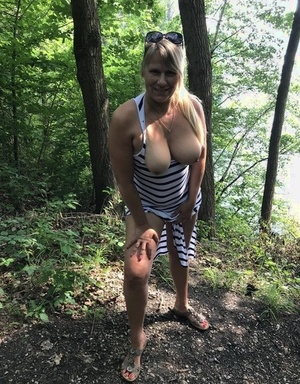 Mature fledgling shows her big boobs and butt on bench in the forest