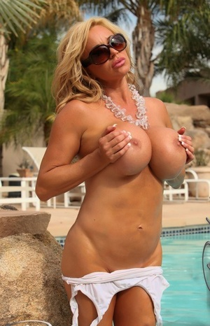 Blonde hottie Rachel Aziani releases her large breasts from wet swimsuit