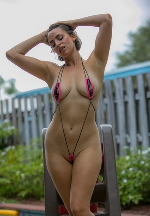 Sexy girl in ass shorts and bikini getting naked to show saggy tits poolside