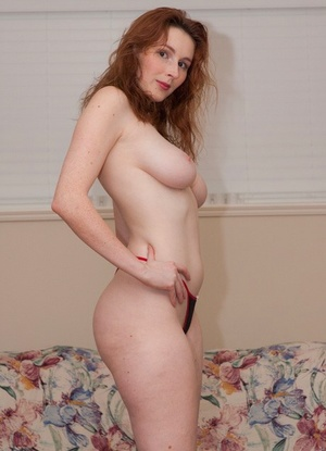 Pale redhead Elli Nude touts hefty tits and donk before taking off a g-string