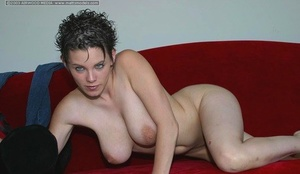 First timer with short hair strips naked on a red sofa for first bare poses