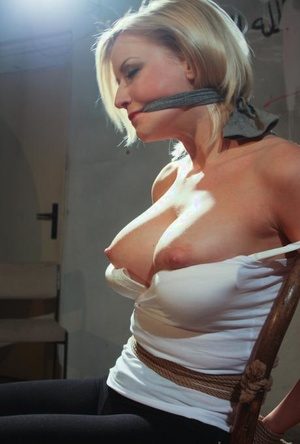 Busty Victoria tied to a chair with her big tits exposed in steamy BDSM sex