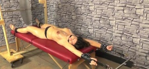 Topless brunette is left cleave gagged and confined to a rubdown table