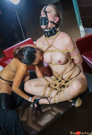 Collared and cable bound blonde damsel is admired by an Asian woman