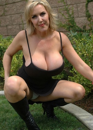 Mature blonde woman unclothes her boots and unleashes her huge baps