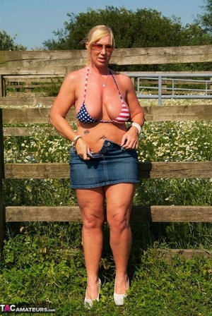 Chesty mature slut Melody sheds swimsuit top outdoors to sun enormous tits