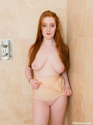 Pale redhead uncovers big naturals before stretching out her slit in shower